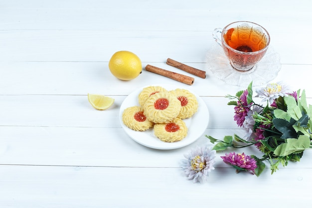 Some cookies, cup of tea with cinnamon, lemon, flowers on white wooden board background, high angle view.