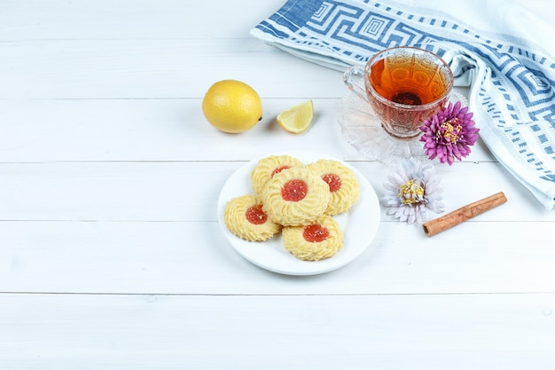 Some cookies, flowers with cinnamon, cup of tea, kitchen towel, lemons on white wooden board background, high angle view.