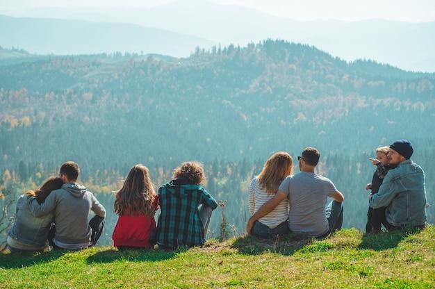 いくつかのカップル旅行者の少年と少女は、山と雲空撮リラックスした崖の上に座って愛と旅行の幸せな感情ライフスタイルのコンセプト。