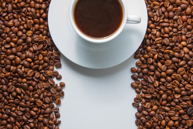 Some a cup of coffee on with coffee beans on background, top view. space for text
