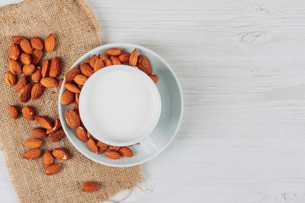 白い木製のミルクのカップと袋の背景、上面の作品。テキスト用の空き容量