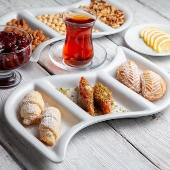 Alcuni deliziosi dessert con tè, noci, marmellata di frutta, fette di limone su fondo di legno bianco, vista di alto angolo.