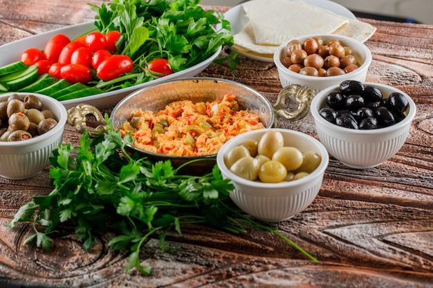 Qualche delizioso pasto con insalata, sottaceti in ciotole in una pentola su superficie di legno