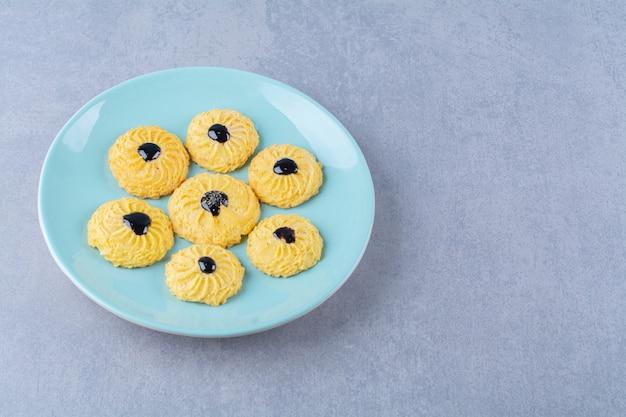 Alcuni deliziosi biscotti gialli con sciroppo di cioccolato su un piatto blu.