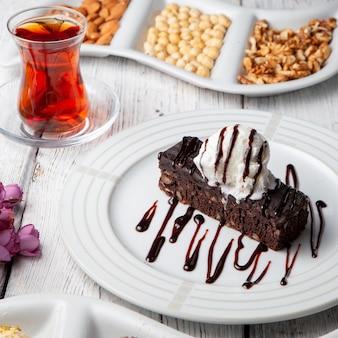 Un certo dessert con tè, dadi in un piatto su fondo di legno bianco, vista dell'angolo alto.