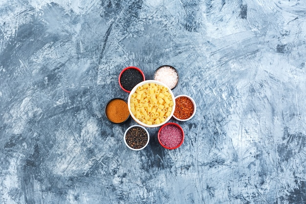 Some ditalini pasta with assorted spices in a bowl on grey plaster background, top view.