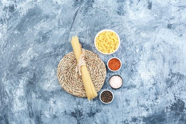 Alcuni ditalini con spaghetti, spezie in una ciotola su intonaco grigio e sfondo tovaglietta di vimini, vista dall'alto.