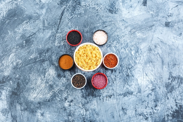 Some ditalini pasta with spices in a bowl on grey plaster background, top view.