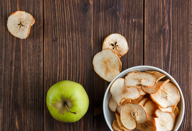 Some dried apples with green one in a bowl on wooden background, top view.