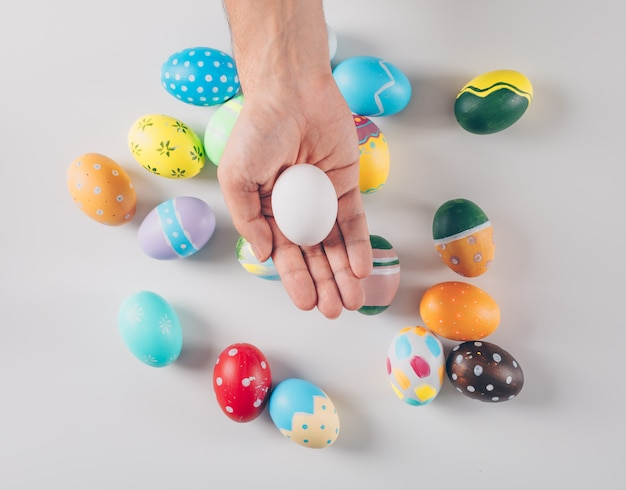 Some easter eggs with man holding one white egg on white background, top view.
