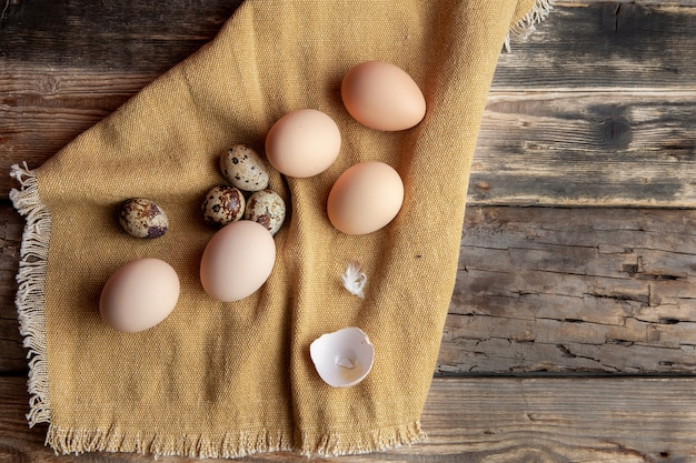 Some eggs with broken one on cloth and dark wooden background, top view.