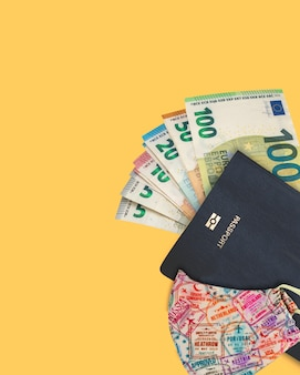 Covid 마스크와 여권이있는 일부 유로 지폐.