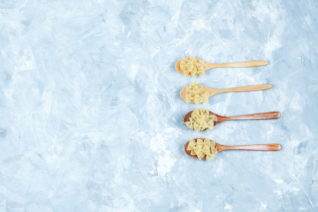 Some farfalle pasta in wooden spoons on grungy grey background, flat lay.