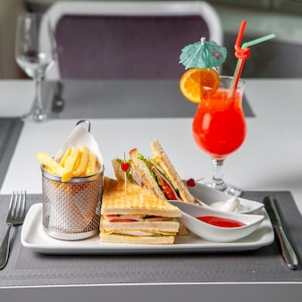 Some fast food with sandwich, french fries, red cocktail, fork and knife on table, side view.