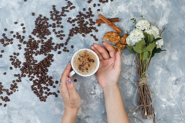 Some female hands holding a cup of coffee with coffee beans, cinnamon sticks, flowers, cookies on grey plaster background, flat lay.