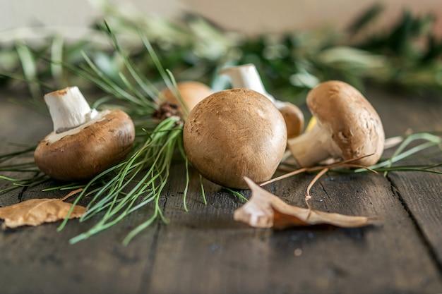 Свежие ароматные коричневые шампиньоны с травой и листьями на натуральном деревянном столе.