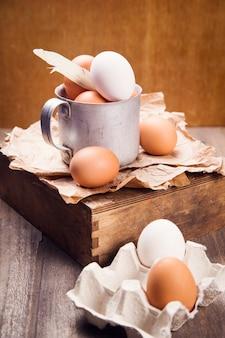 Некоторые свежие коричневые и белые яйца в старой чашке в студии