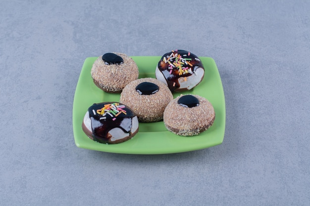 Some of fresh chocolate doughnuts with sprinkles on a green plate.