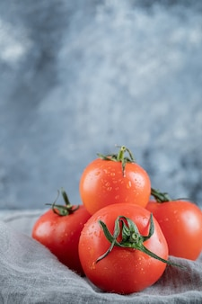Some of fresh tomatoes on a gray tablecloth .