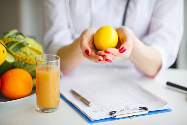 栄養士のテーブルにリンゴ、キウイ、レモン、ベリーなどの果物