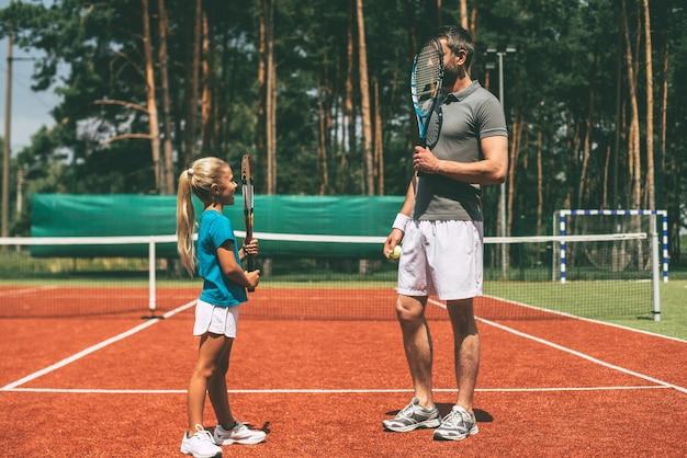 ゲームの前にいくつかの楽しみ。一緒にテニスコートに立っている間、スポーツウェアを着て、顔の前でテニスラケットを運ぶ小さなブロンドの髪の少女と彼女の父親の全長