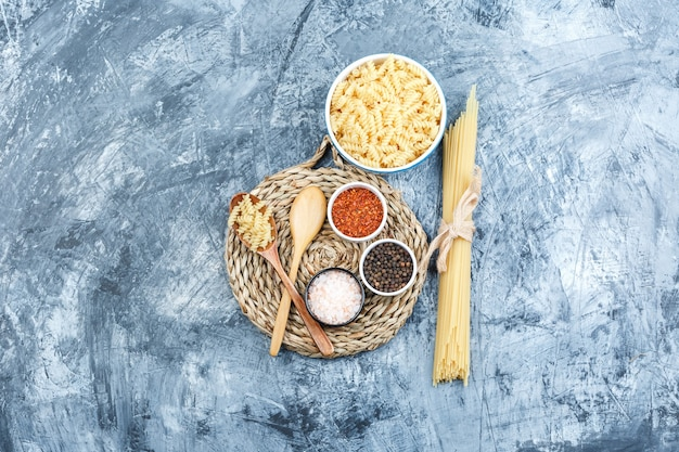 Some fusilli pasta with spaghetti, wooden spoons, spices in a bowl on grey plaster and wicker placemat background, top view.