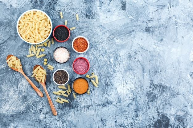 Some fusilli pasta with spices in bowl and wooden spoons on grey plaster background, top view.