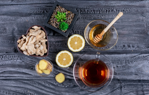 Some ginger and honey in a bowls with ginger slices, lemon on dark wooden background, top view.