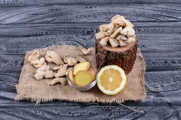 Some ginger with lemon and ginger slices on wood stub, sack cloth and dark wooden background, high angle view.