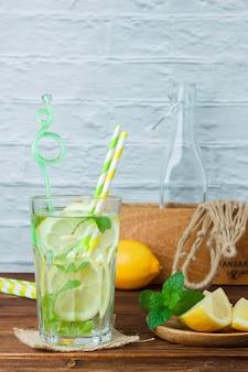 Стакан лимонного сока с деревянным ящиком и веревкой на деревянной и белой поверхности, вид сбоку. скопировать место для текста