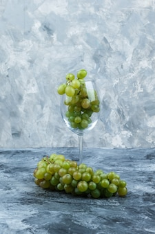 Some glass of white grapes on dark and light blue marble background, close-up.