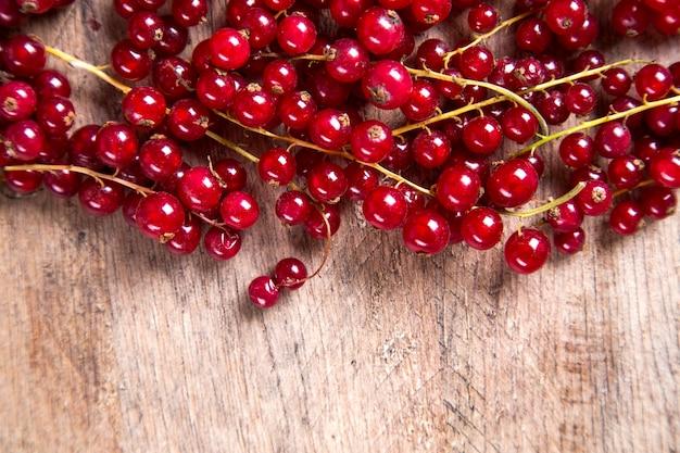 木製のテーブルの上にいくつかのグーズベリー、ラズベリー、イチゴ、ブルーベリー。