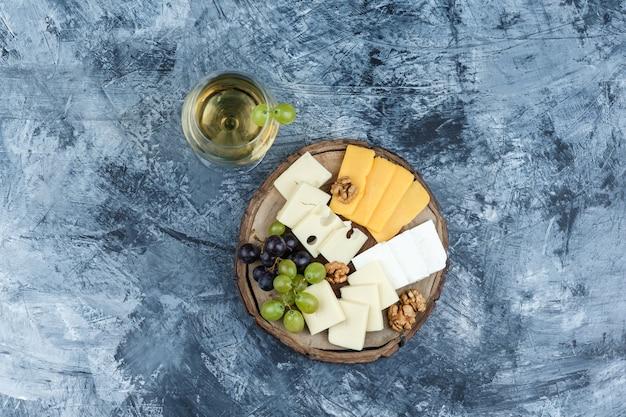 Alcune uve con un bicchiere di vino, formaggio, noci su intonaco e sfondo di legno, vista dall'alto.