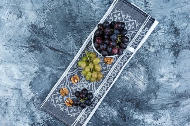 グランジとキッチンタオルの背景、上面図の白いカップにクルミといくつかのブドウ。