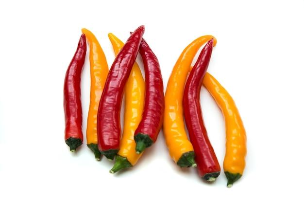 白で隔離されるいくつかの緑と黄色の唐辛子野菜。