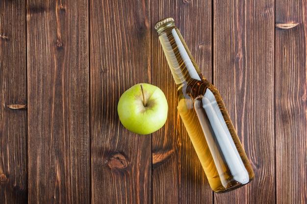 Una certa mela verde con il succo di mele su fondo di legno, disposizione piana. spazio per il testo