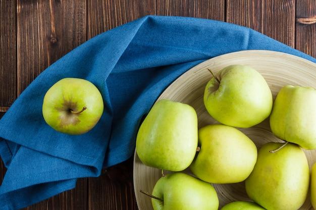 Alcune mele verdi in un piatto sul panno blu e sul fondo di legno, vista superiore.