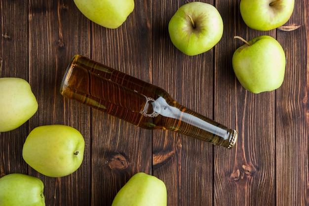 Alcune mele verdi con il succo di mele su fondo di legno, vista superiore.