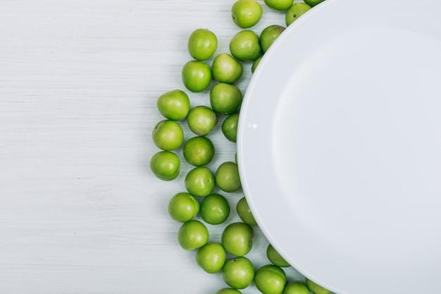 白い木製の背景の空の皿といくつかの緑のチェリープラムクローズアップ。テキストのコピースペース