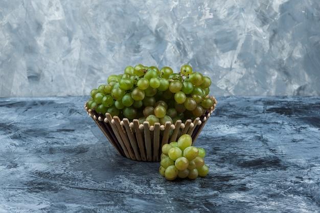 지저분한 석고 배경, 측면보기에 바구니에 일부 녹색 포도.