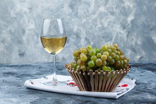 Alcune uve verdi con un bicchiere di vino in un cesto su intonaco sgangherato e asciugatutto sfondo, vista laterale.