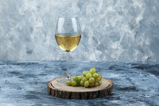 Alcune uve verdi con un bicchiere di vino su intonaco sgangherato e sfondo pezzo di legno, vista laterale.