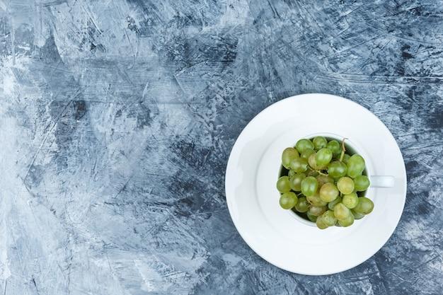 지저분한 석고 배경, 평면도에 흰색 컵에 접시와 일부 녹색 포도.