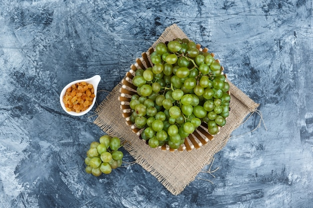 Some green grapes with raisins in a basket on grunge and piece of sack background, flat lay.