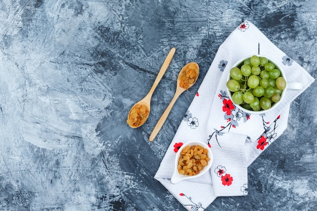 Some green grapes with raisins in a white cup on grungy plaster and kitchen towel background, top view.