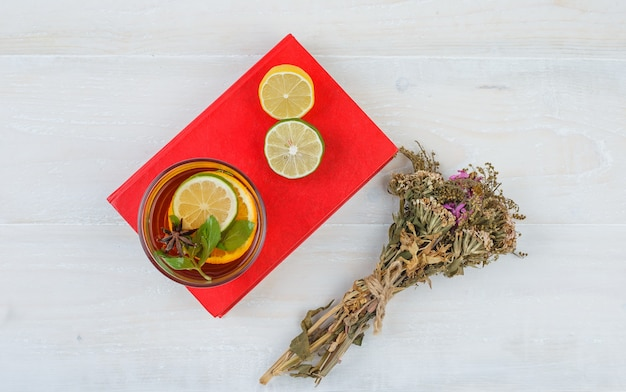 Some herbal tea and citrus fruits with a flower bouquet on a red placemat
