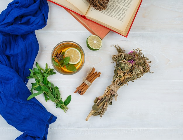 Some herbal tea and flowers with books, lemon, spices and blue scarf on white surface