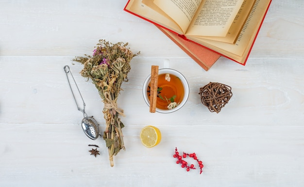 Some herbal tea and flowers with books,lemon,tea strainer and spices on white surface