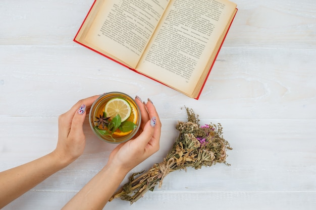Some herbal tea with books and flowers on white surface