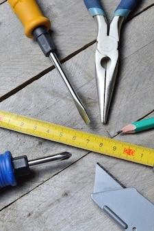 いくつかの家の修理ツールは、木製の背景にあります。閉じる。